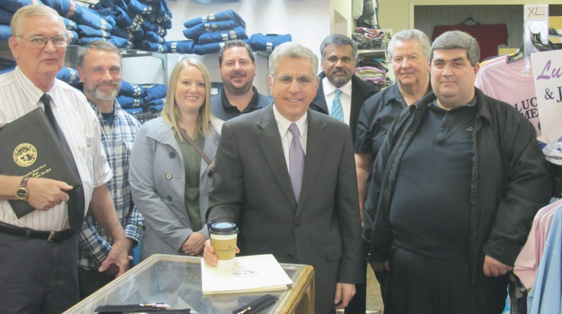 From left, Cliff Powers, Lander's Men's Store owner; Michael and Sarah Bigney, Crown Street Roasting Company owners;  Sammy Lisciandro, The Pub manager; Jamestown Mayor Sam Teresi; Salim Sarvaiya, Southside Pharmacy pharmacist/owner; John Lisciandro, Lisandro's owner; and Sergey Khodzhayan, Fresco Pizza and Wings owner; during the presentation of a city proclamation commemorating Small Business Saturday, which will be celebrated in the city on Nov. 25. P-J photo by Dennis Phillips