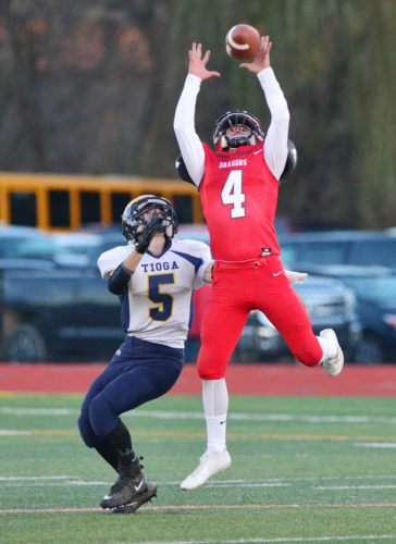 Maple Grove's Easton Tanner (4) leaps high for an interception in front of Tioga's Nick Klossner during Friday's New York State Public High School Athletic Association Class D semifinal football game at Ty Cobb Stadium at Union-Endicott High School. P-J photo by Scott Reagle