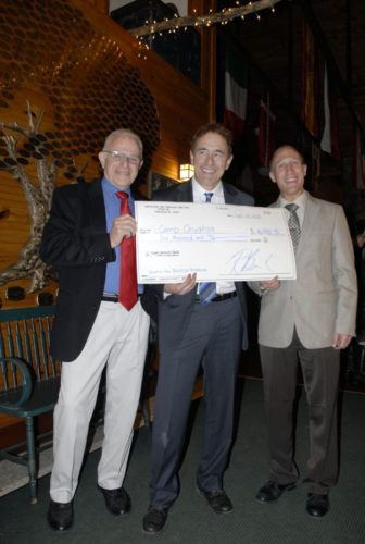 Kurt Gustafson and Dr. Robert Berke, co-directors of the BigFish Triathlon, are pictured presenting Jon O'Brien, Camp Onyahsa director, with a check.