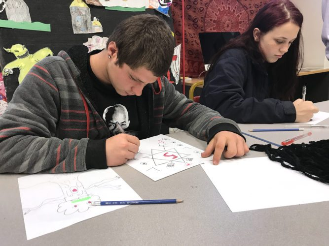 Jamestown High School students, Branden Ryan and Hailey Axford work on drawings during art class at the Infinity Visual & Performing Arts Center.