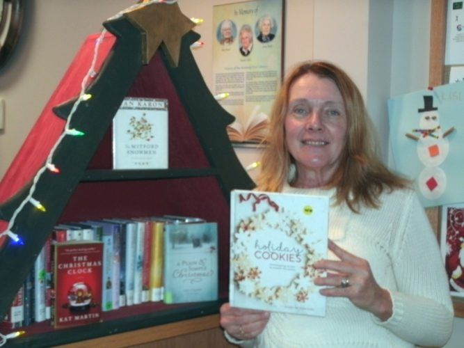 Kennedy Free Library Director Maggie Ruth stands by the special handmade Christmas display of books for the holidays.