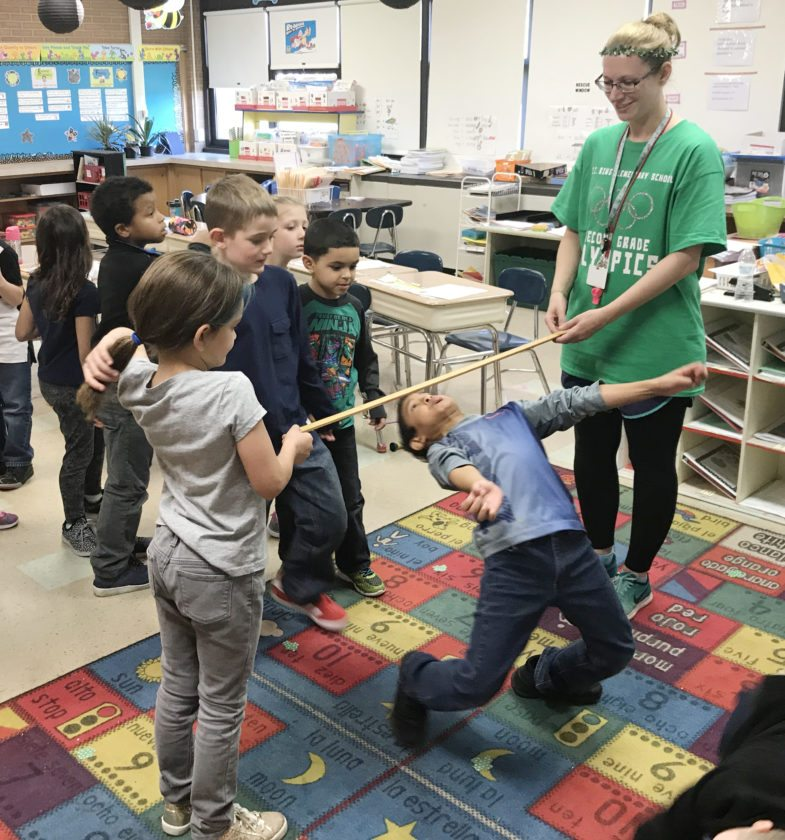Ring Elementary School second grader, Ernie Carrasquillo, does the limbo under a pole held by teacher, Andrea Norene and fellow student, Maleeya McGaughy, during their recent grade-level Olympics.