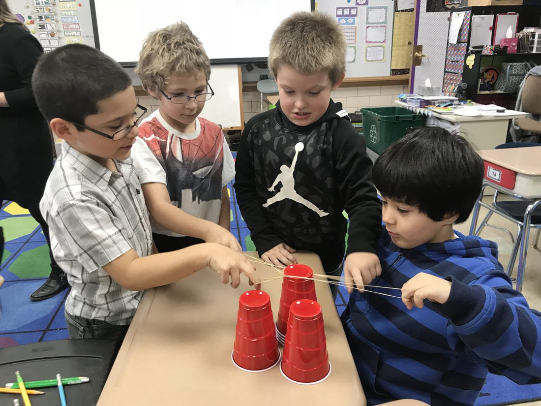 Ring Elementary School second graders, Steven Best, James McCauley, Sylis Caruso and Talcon Davis perform the Solo Cup Challenge during a recent grade-level Olympics using mathematical thinking and reasoning to solve various riddles and complete challenges.