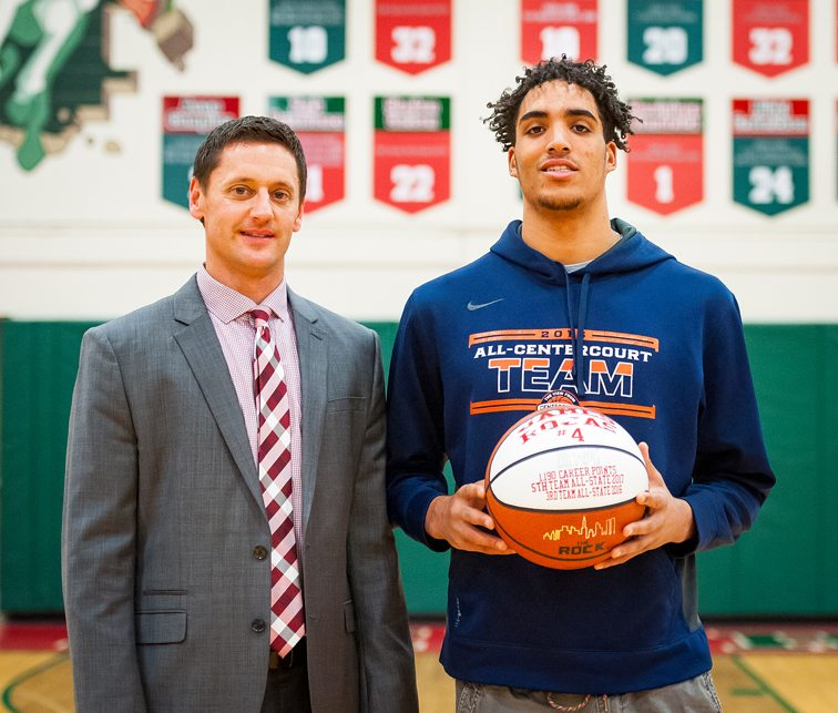 James Rojas, right, is presented a ball commemorating his induction on to the Jamestown High School Wall of Fame at McElrath Gymnasium on Tuesday night. Joining him is JHSvarsity boys basketball coach Ben Drake. Now a freshman at Hutchinson (Kan.) Community College, Rojas finished his career as only the second player in Red Raider history to have 1,000 career points, 500 rebounds, 100 assists and 100 steals. P-J photo by Valory S. Isaacson