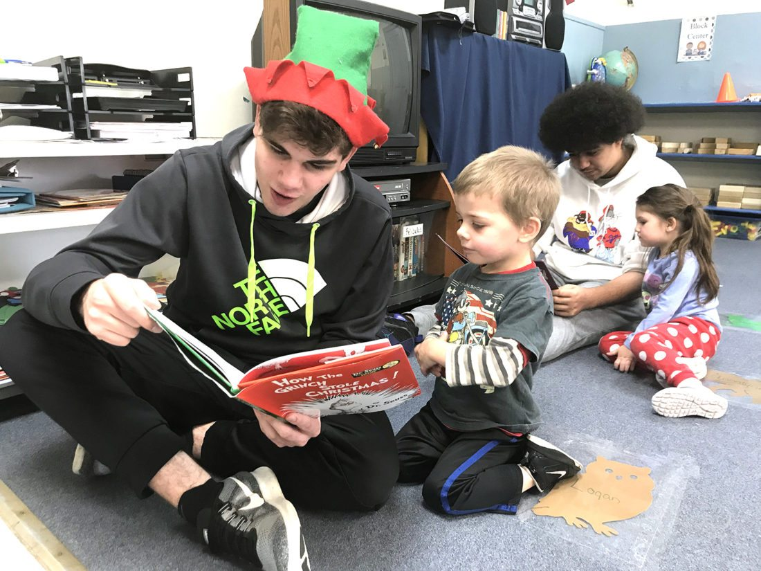 """Jamestown High School students, Seneca Parker and Kenard Marion, read to students in the YWCA Early Childhood Education Program for a service project as part of their class, """"Justice for All."""""""