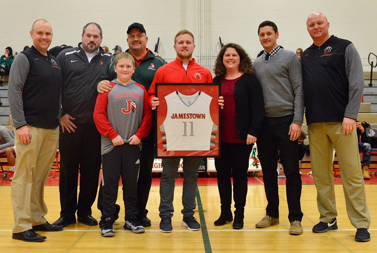 Zack Panebianco, center, had his jersey retired before Jamestown High School's game against Fredonia in the United Way Showcase at McElrath Gymnasium on Saturday night. Joining him in the presentation are, from the left, junior varsity coach Billy Miley, freshman coach Tage Hall, brother Carson Panebianco, father Mark Panebianco, mother Jenn Panebianco, varsity head coach Ben Drake and varsity assistant coach Marty Stockwell. Panebianco is the fifth player in school history to have his jersey retired, joining Donn Johnston, Terry Chili, Justin Johnson and Maceo Wofford in that select fraternity. A two-time Post-Journal Player of the Year and the Western New York Player of the Year as a senior, Panebianco is the only Red Raider to be named all-state three times (seventh team as a sophomore, fourth team as a junior, and second team as a senior). He is currently a junior on the SUNY Geneseo basketball team. P-J photo by Scott Reagle