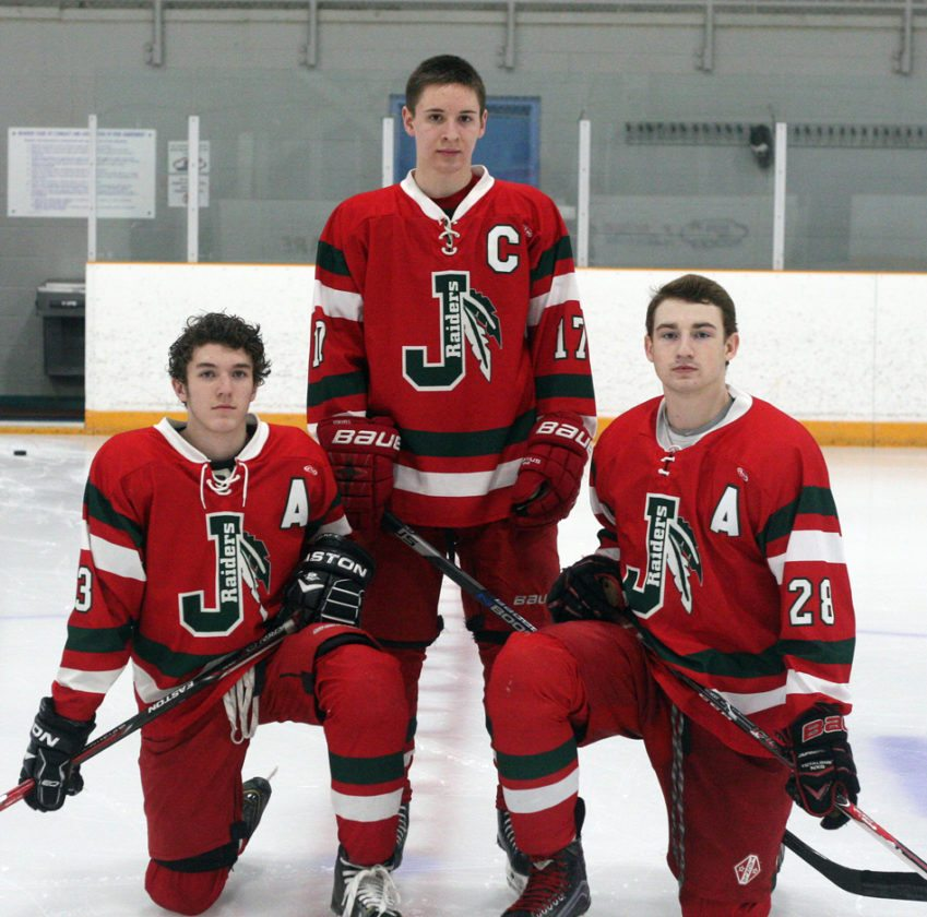 Jamestown Raiders captain Jacob Gerace, standing, is flanked by assistant captains Cade Poston, left, and Cole Snyder. P-J photo by Jay Young