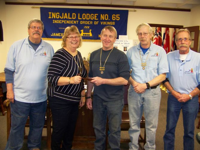Out-going Viking Chief, Jane Fosberg, is handing gravel to newly elected Viking Chief Doug Sanders. Members of installation team: Bryan Nelson, Bill Peterson and Tim Fagerstom.