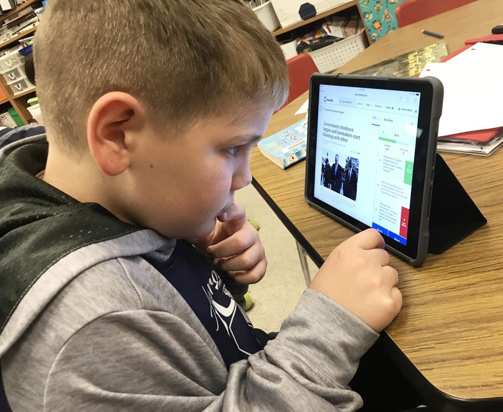 Washington Middle School fifth grader, Adam Kubera, reads about the government shutdown on his iPad through www.newsela.com in Deb Rein's class.
