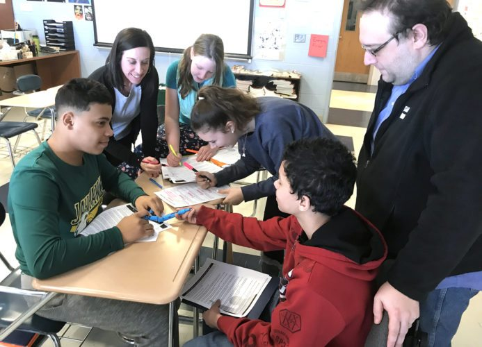 Washington Middle School students Ablet Rosario Rodriguez, Cathrine Tompkins, Madison Taylor, and Dylan Ocasio work with co-teachers Sarah Stewart (English as a New Language) and Jason Williams (ELA) on a project during ELA class.
