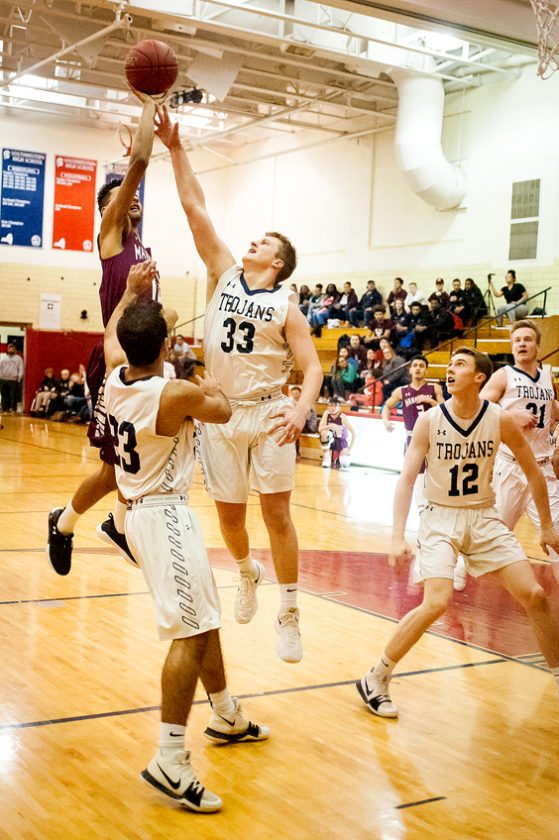 Dunkirk's Tyrese Kristian-Johnson shoots over Southwestern's Cooper Pannes (33) while Trojans Faizan Munir (23) and Derek Miller (12) look on during Tuesday's CCAA Division 1 West game at Southwestern. P-J photo by Valory S. Isaacson