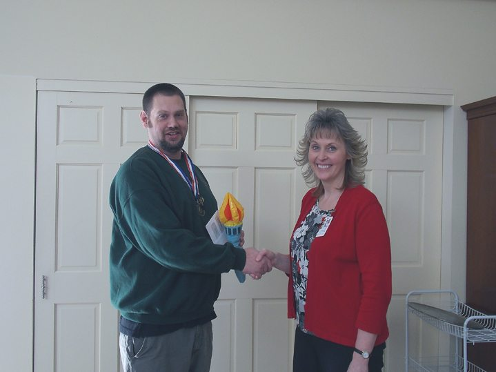 Mark Akam, Heritage Ministries employee of the year at The Green in Greenhurst, shakes the hand of Cheryl Farr, The Green in Greenhurst administrator. Submitted photo