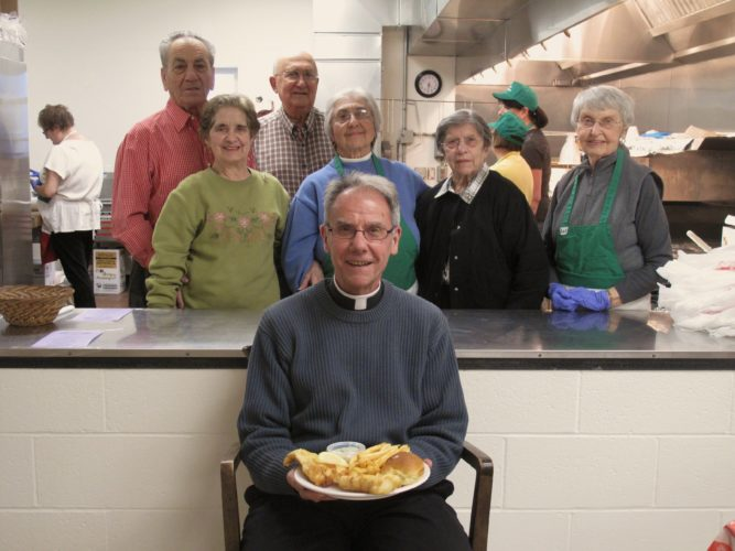 The Rev. Dennis Mende of Holy Apostles Parish displays the first Lenten Fish Fry of the season at St. John's Church in Jamestown. Pictured from left behind Mende are Joe Lisciandro, Carol Lisciandro, Bill Gullotti, Diana Purtell, Tina Russo and Nancy Cummings. P-J photo by Katrina Fuller