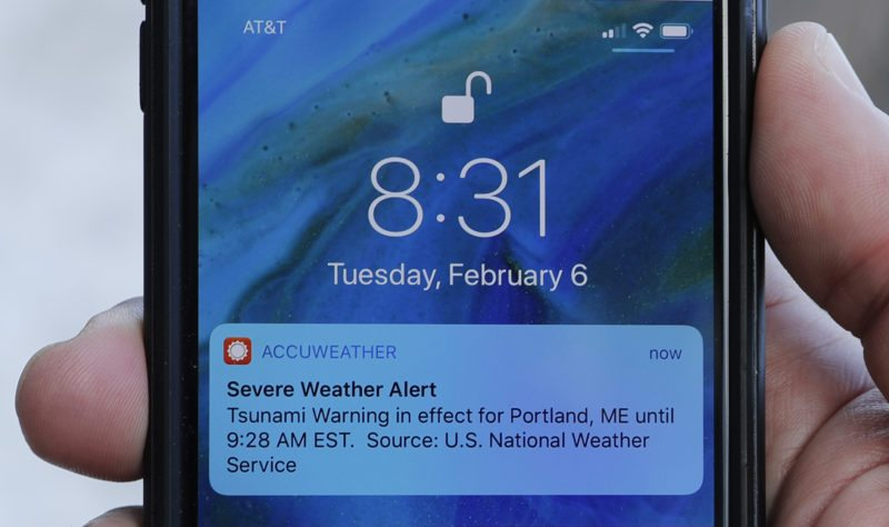 In this Thursday, Feb. 8, 2018 photo Jeremy DaRos shows the erroneous tsunami alert he received on his phone on Tuesday, Feb. 6, 2018, in Portland, Maine. DeRos, who lives near the water, said he is concerned that people won't take seriously the emergency alerts they get in an actual crisis. (AP Photo/Robert F. Bukaty)