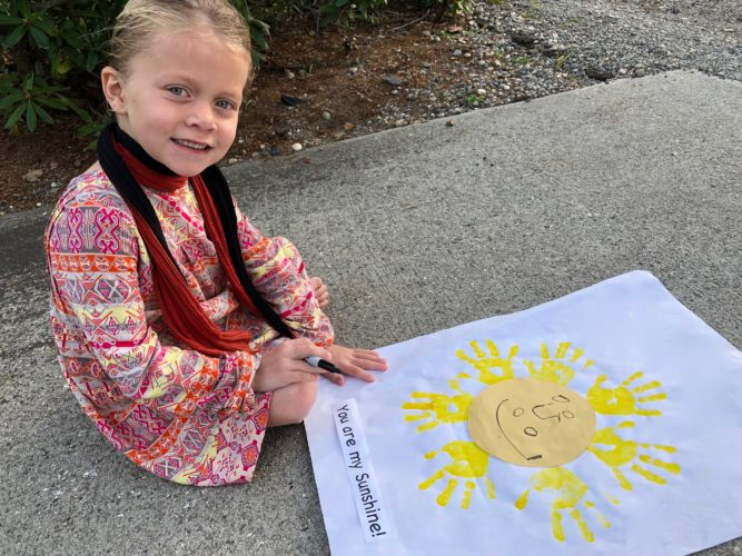 "Eva Holmlund, 5, adds details to a sunshine greeting featuring her ""sunray"" handprints for her grandmother."