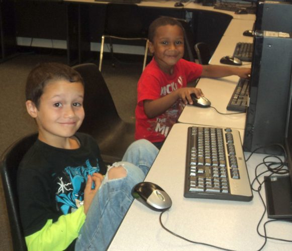 Two WCD Boys & Girls Club members enjoy the computer lab at the Club. The Club will be open during the winter break.
