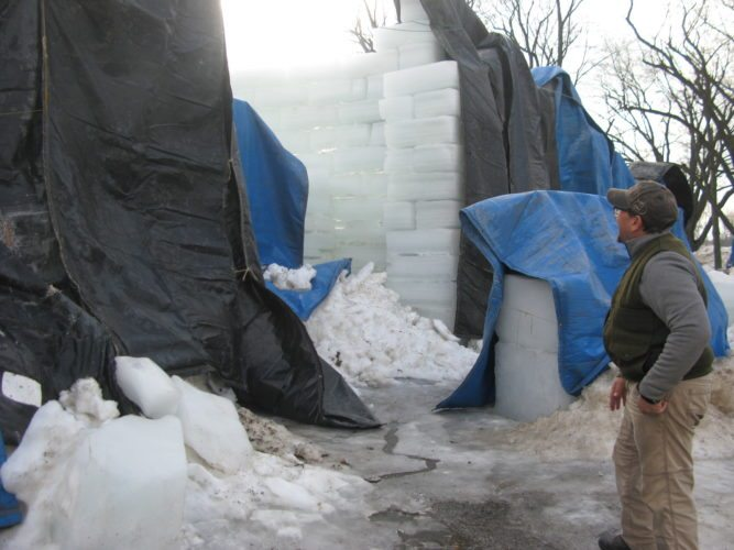 Nick Andriaccio looks on T hursday as a portion of the ice  castle is covered with tarps to  prevent too much melting. The  winter festival begins today in  the village.  P-J photo by Eric Tichy