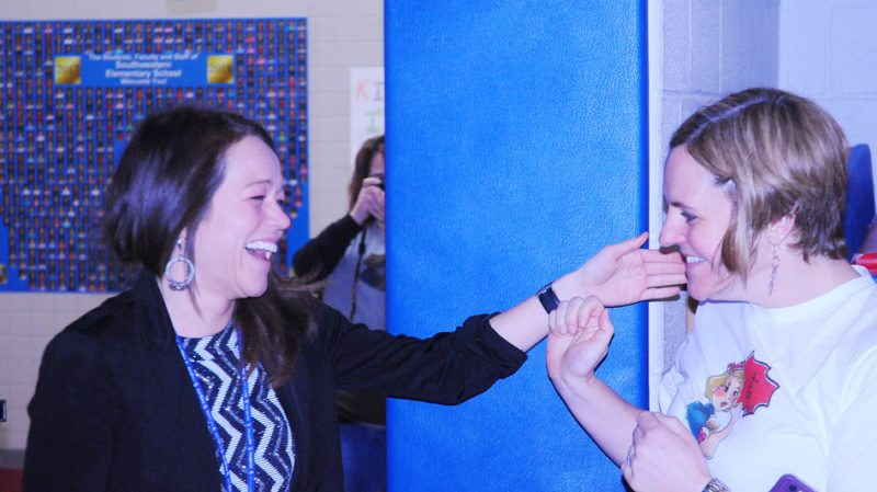 Brooke Adams, assistant elementary/high school principal at Southwestern Central School, left, is congratulated by Molly Moore, the director of instructional services, at a surprise assembly at the elementary school on Thursday morning. The celebration was in honor of Adams trip to Japan where she'll run in the Tokyo Marathon next week, which completes her World Marathon Majors odyssey. P-J photo by Scott Kindberg