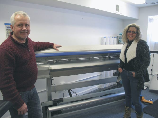 Randy Ridgeway and Bonnie Beightol of Top Shop have reopened their store at 117 Chautauqua Ave. in Lakewood. The owners are pictured in front of their new Rolan 54-inch printer and plotter.  P-J photo by Katrina Fuller