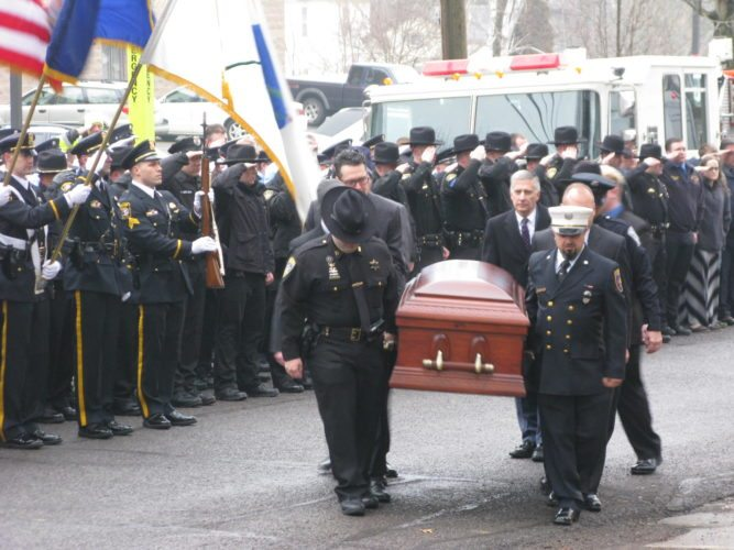 The remains of Michael Seeley, a Chautauqua County sheriff's deputy and Bemus Point firefighter, are carried into the First Lutheran Church in Jamestown on Friday. Seeley died Feb. 9 after battling leukemia. More than 200 firefighters, police officers, emergency workers, friends and family members gathered at the church for his funeral.  P-J photo by Eric Tichy