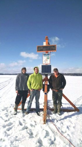 Chautauqua Lake Association volunteers pose with the ice pick tripod on Chautauqua Lake after putting it into position for its annual contest. The pick is located on the ice in front of the Lawson Center in Bemus Bay.  Submitted photo
