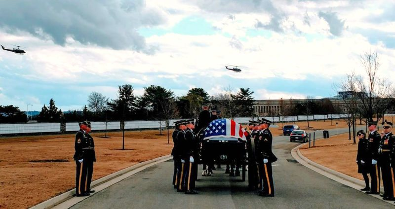 The casket of Maj. Michael Lopriore, U.S. Army retired, approaches its final resting spot at Arlington National Cemetery as two Huey (UH-1) helicopters fly overhead. The Huey was Lopriore's primary aircraft during his service tours in Vietnam. Submitted photo