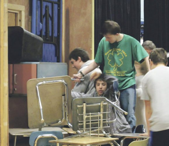 Warren Area High School ninth graders barricade a door with classroom items and equipment during a lockdown training Thursday morning. Photo by Brian Ferry