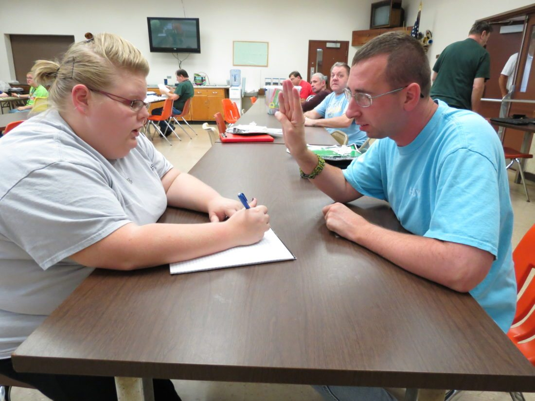 Matt Elcessor goes over some math problems with Ashley Burtag, a job skills trainer at the Hancock County Sheltered Workshop. (Photo by Stephen Huba)