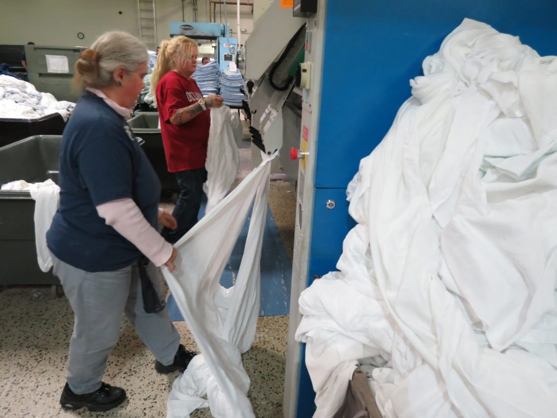 Jamie Capito (left), of Chester, and Christina Harford, of Weirton, put sheets into an automated spreader/feeder at the Hancock Laundry, a business of the Hancock County Sheltered Workshop. (Photo by Stephen Huba)
