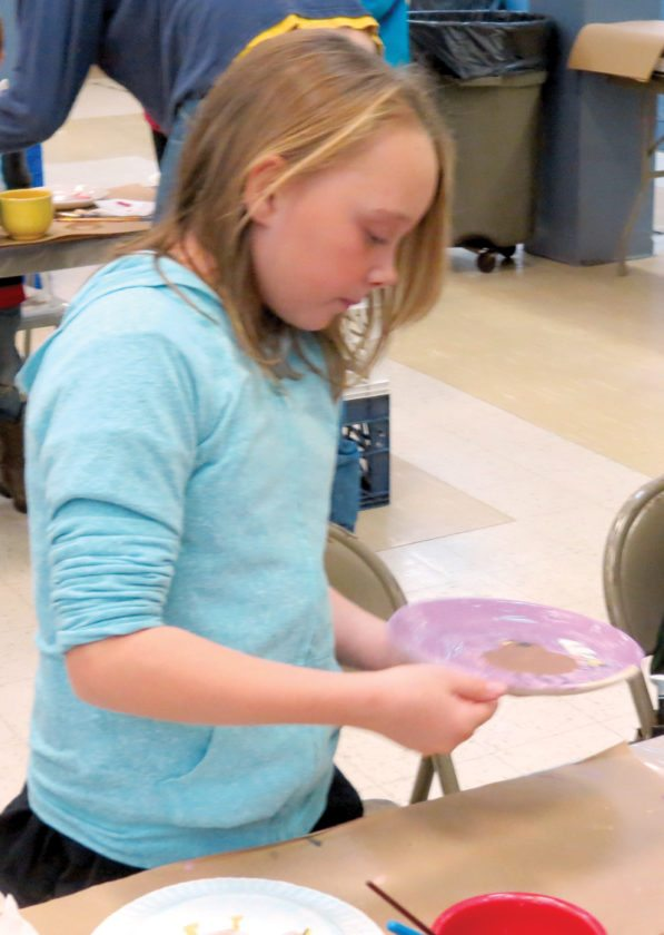 Keirstyn Curtis, 10, gets ready to turn in her finished plate, which she artistically painted during Homer Laughlin's annual Paint-a-Plate event Saturday at the Wells Building in Newell. (Photo by Steve Rappach)