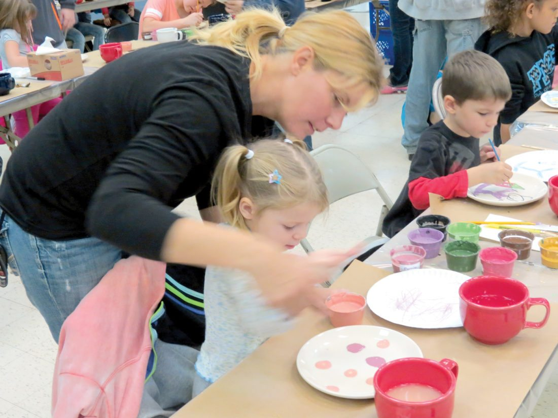 Debbie Koby helps her 2-year-old daughter Olivia with her plate Saturday during  the eighth annual Paint-a-Plate event. (Photo by Steve Rappach)