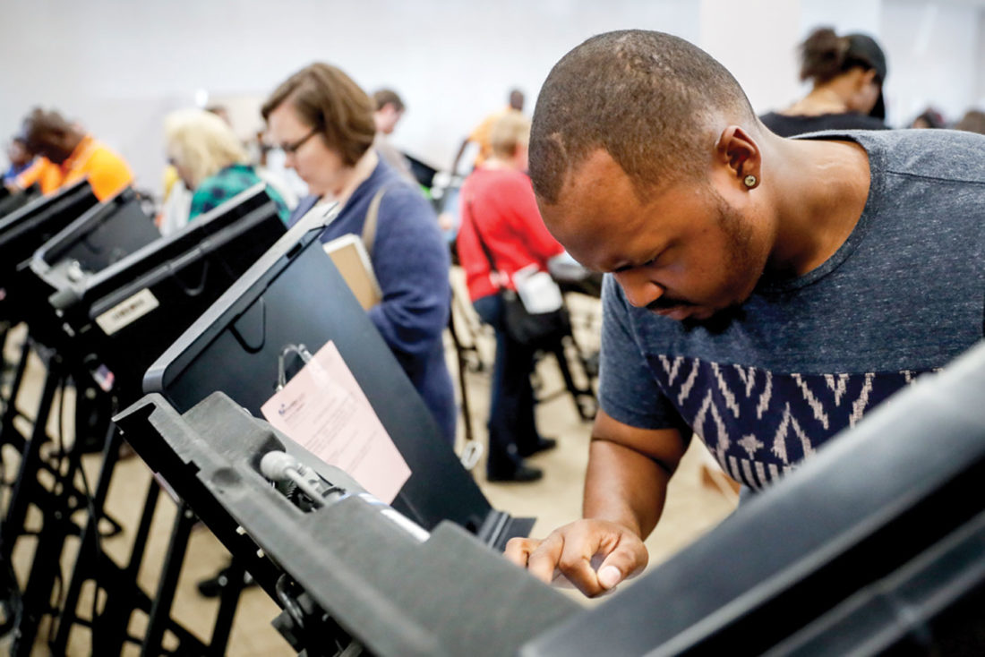 Elijah Ransom of Columbus, votes early Monday at the Franklin County Board of Elections in Columbus, Ohio. Heavy turnout has caused long lines as voters take advantage of their last opportunity to vote before election day. (AP Photo/John Minchillo)
