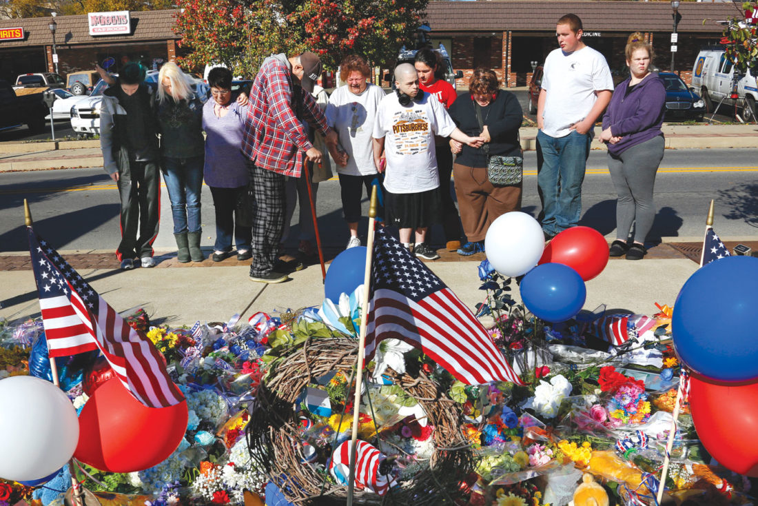 A group prays in front of a makeshift memorial for the Canonsburg Police officers who were shot when they responded to a domestic call early Thursday, Nov 10, 2016, in Canonsburg, Pa. (AP Photo/Gene J. Puskar)
