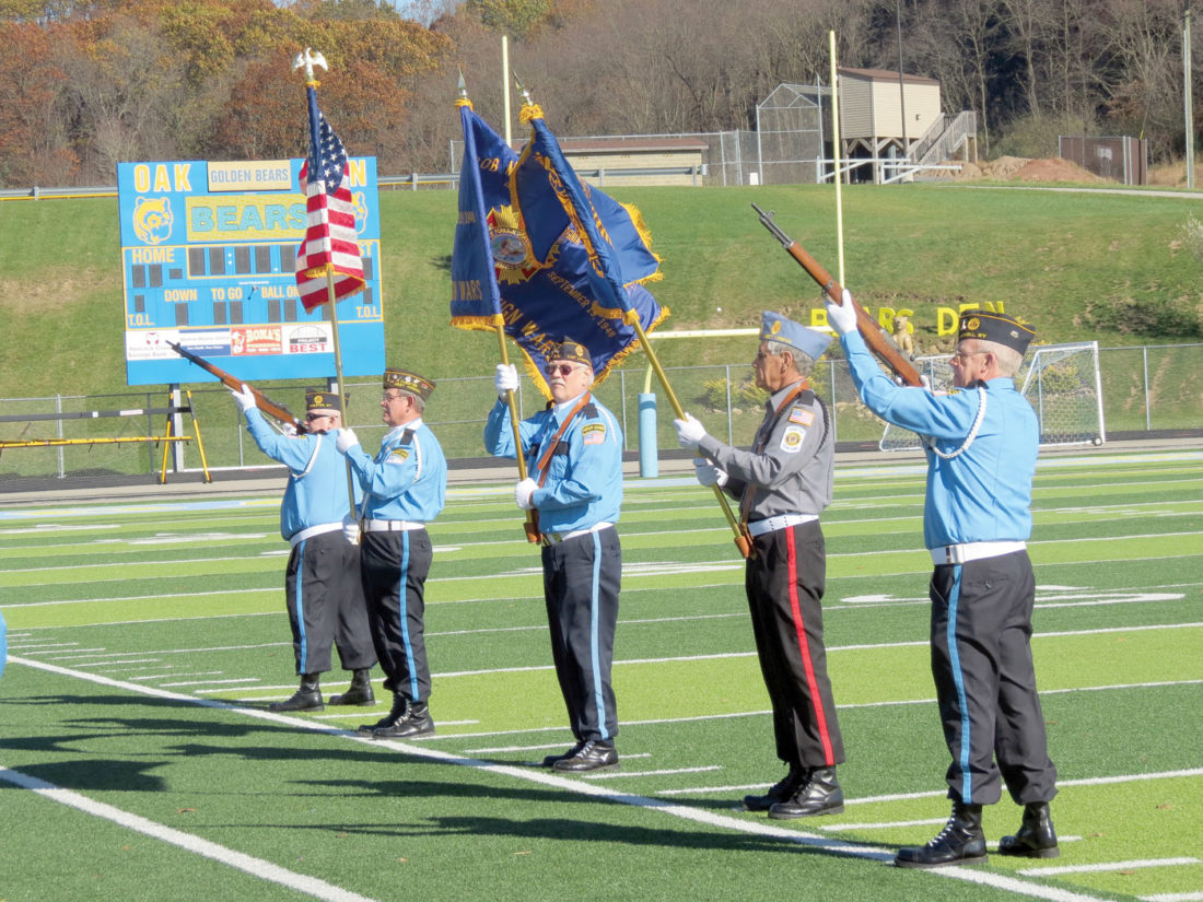 Members of the Tri-State Burial Color Guard hold a gun salute Thursday afternoon during the opening ceremony of Oak Glen High School's walk for solidarity, in honor of Veterans Day, at the high school stadium. Organized by the high school's Student Council, the event was held to honor those who have served in the Armed Forces, and coincided with a previous drive to which donations were collected for the Fisher House Foundation. (Photo by Steve Rappach)