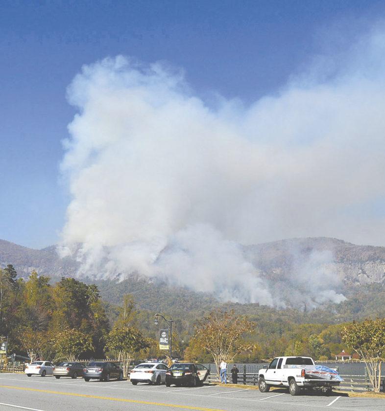 People take photos of a wildfire burning near Lake Lure, N.C., Thursday, Nov. 10, 2016. (Patrick Sullivan/The Times-News via AP)