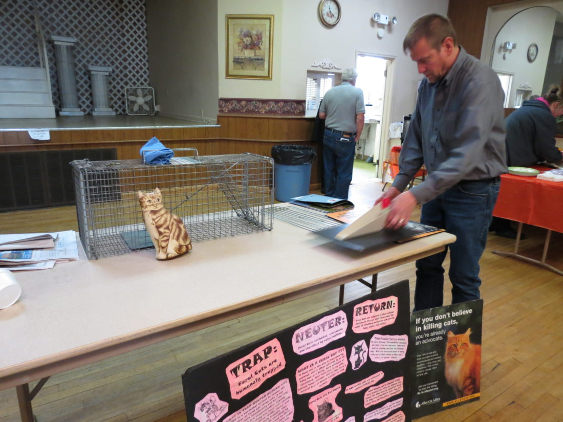 Toby Franks, of Canton, Ohio, sets up a feral cat display on Saturday prior to his talk at Victorian Hall in Weirton. Franks is an expert in the trap-neuter-return, or TNR, method of controlling the feral cat population. The cage shown is the kind that is commonly used in TNR programs. (Photo by Stephen Huba)