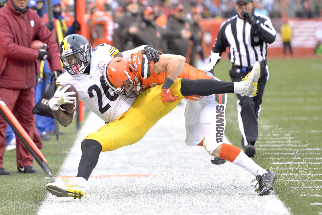 Pittsburgh Steelers running back Le'Veon Bell (26) is shoved out of bounds by Cleveland Browns' defensive back Ed Reynolds II (39) during the second half of an NFL football game in Cleveland, Sunday, Nov. 20, 2016. The Steelers won 24-9. (AP Photo/David Richard)
