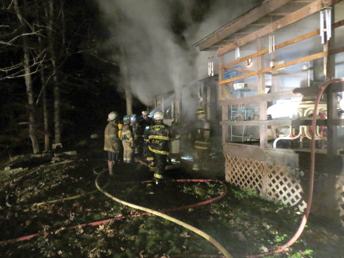 Liverpool Township fire crews worked to extinguish a blaze at a mobile home on Oak Grove Road Tuesday evening. Two adults, believed to be middle aged, were able to escape the home and were picked up by family members. The house, according to Liverpool Township Fire Chief Dave Ward, is considered a total loss. (Photo by Steve Rappach)
