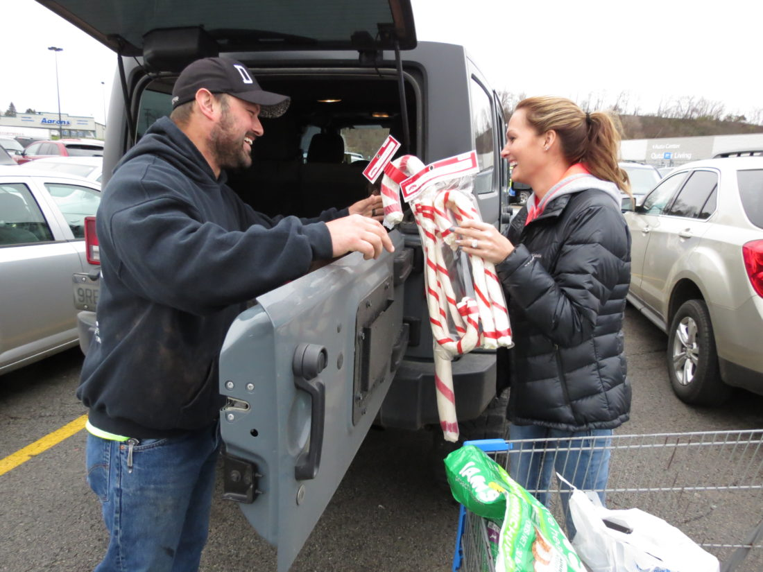 Chad Dlugopolski, of New Cumberland, and his wife, Nina, load up their SUV with Black Friday purchases from the Calcutta Walmart. Dlugopolski said he got a good deal on a radio-controlled truck and dog supplies. Despite changes brought on by online retailers, Black Friday remains the largest Christmas shopping day of the year. (Photo by Stephen Huba)