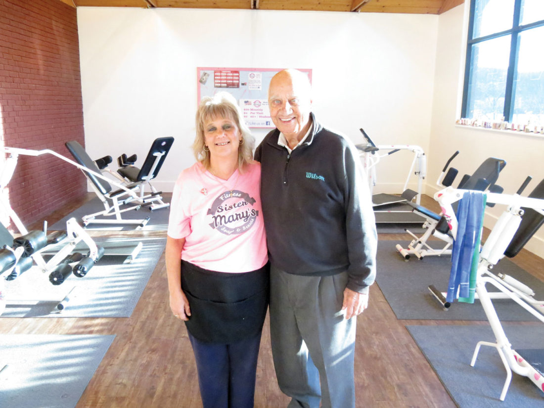 Mary Frazier (left), owner and operator of Sister Mary's Fitness and Boutique on Wells Avenue, and her father, former Wellsville Mayor Joe LaScola, showcase the several fitness machines available at the gym that women can use. The facility is open 10 a.m.-6 p.m. Mondays through Fridays, and an Open House will take place during business hours Nov. 28 through Dec. 2. (Photo by Steve Rappach)