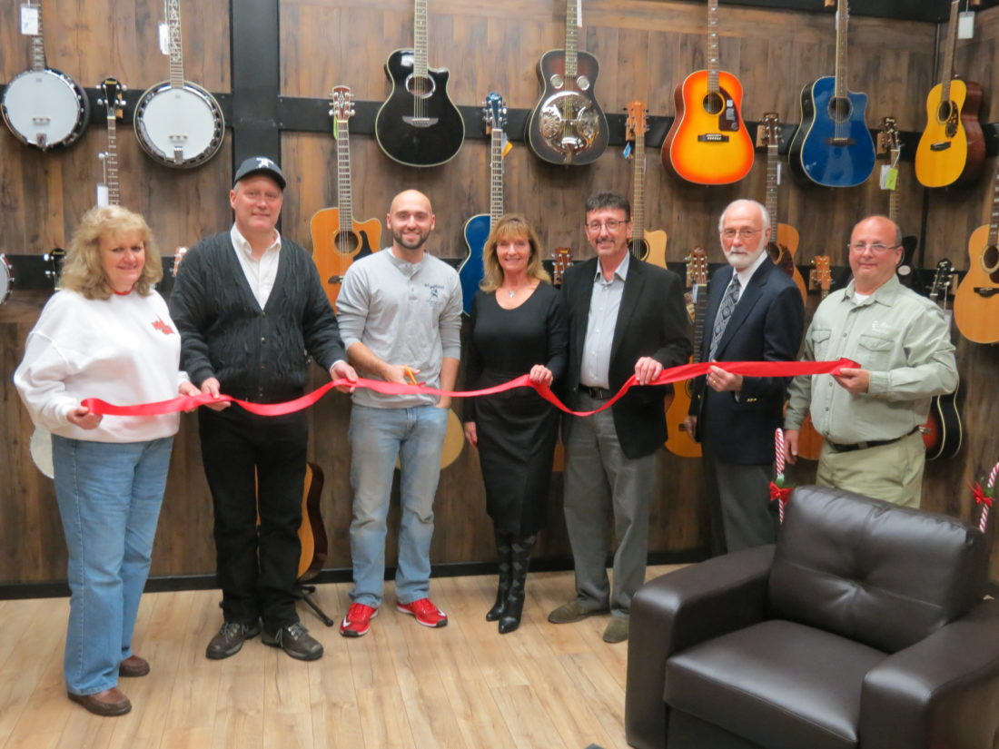 The grand re-opening of DC Music Store, at its new location in the Dunham's Plaza, took place Monday. The music store, which features a wide variety of musical instruments and various brands of guitars, basses, pianos, drum kits and more, is now located at the former Family Video location inside the plaza. Those pictured in the ribbon-cutting event were (from left) Rosemary Byers, co-owners Dave Byers and Zach Byers, St. Clair Township fiscal officer Deborah Dawson and St. Clair Township trustees James Sabatini, James Hall and Robert Swickard. (Photo by Steve Rappach)