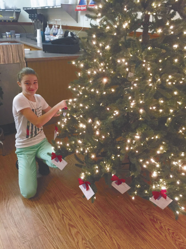 "Chester Arts Club is sponsoring the ""Giving Tree"" for WV Veterans Home Vets. They have placed a Christmas Giving Tree at Crickster's Family Restaurant. The Christmas tree was donated by Joanna Hobbs, Chester Arts Club President, and was decorated by Marlene Fleming and her visiting granddaughter, Abby Cadwallader (pictured)."