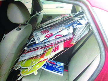 A stack of advertising signs are seen in the back seat of a vehicle where they were allegedly placed by Megan Jo Williams of Rogers, who told witnesses she was sick of the signs cluttering up Calcutta. She was arrested by St. Clair Township Police. (Photo courtesy of St. Clair Township Police)
