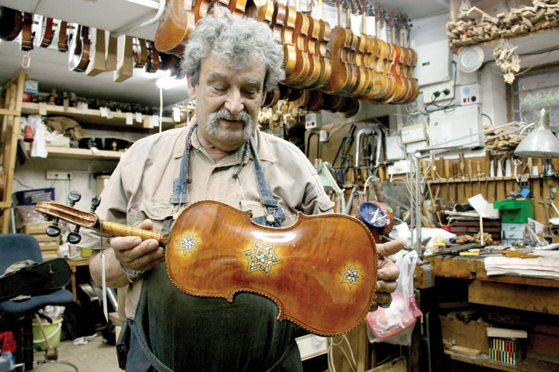 Master violinmaker Amnon Weinstein holds one of the violins recovered from the Holocaust as part of