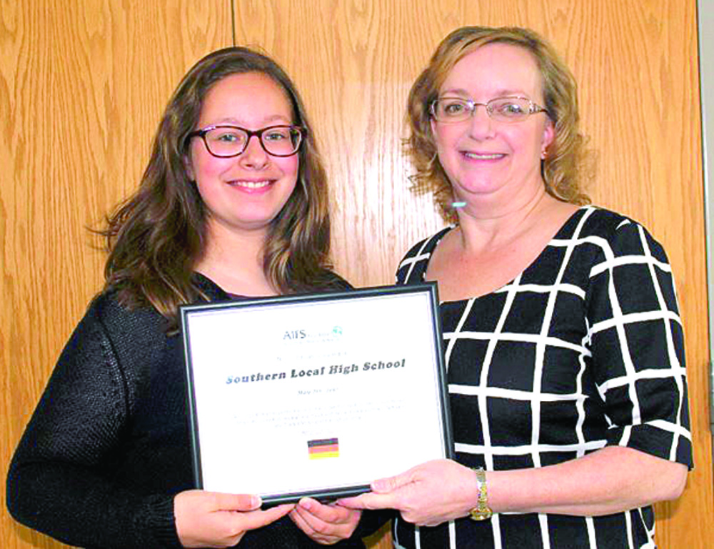 "Southern Local High School was recognized by the American Institute for Foreign Study (AIFS) Foundation for participating in its Academic Year in America exchange program during 2017. The school hosted foreign exchange student junior Justine Eckel of Germany, who resided with a family in Wellsville while gaining an education at SLHS. Eckels, pictured presenting the certificate to SLHS Guidance Counselor Nancy Saling, will return to her home country in June and said she has enjoyed her American experience, from attending homecoming and prom to participating in the Art Club and FFA. The AIFS exchange program ""promotes mutual understanding, respect and tolerance between the United States and partner countries,"" a release states. (Submitted photo)"