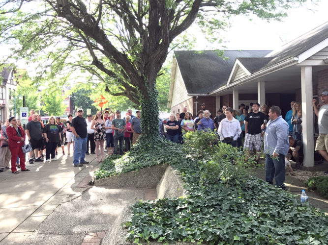 A crowd gathered outside Family Care Ministries in East Liverpool Monday evening for a prayer vigil led by Josh and Donny Lytle. They prayed for those whose lives are being controlled by addictions, for police officers, city officials and the community. (Photo by Jo Ann Bobby-Gilbert)