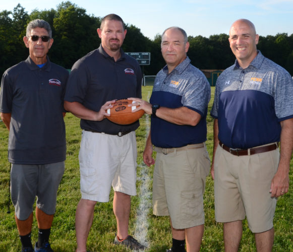 The 38th annual Penn-Ohio Stateline Classic will be held today at Geneva College. Leading the festivities (from left) will be Ohio head coach Jim Tsilimos of Lisbon, Ohio game director Nick Haught, Pennsylvania game director Curt Agostinelli and Pennsylvania head coach Joe Lamenza of Blackhawk. Player introductions begin at 6:30 p.m. with the game set to kickoff at 7 p.m. (Photo by Patti Schaeffer)