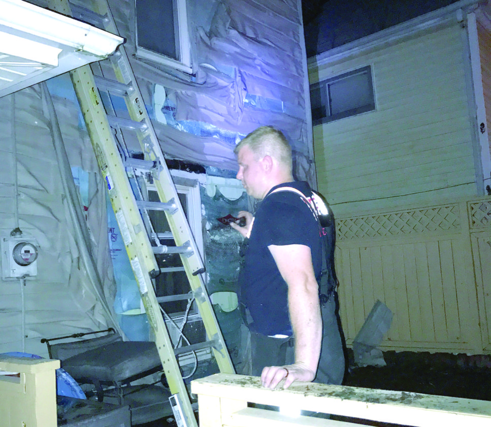 East Liverpool firefighter Tim Grantz uses a flashlight to look over the rear of a Riverview Street house where the vinyl siding was melted from a blaze in its detached garage Saturday night. (Photo by Jo Ann Bobby-Gilbert)