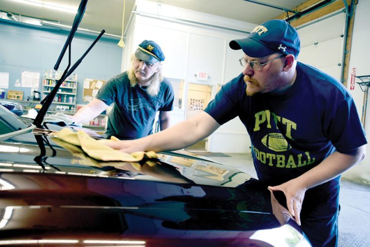 Jamie Gordon (front) puts the final polish on a car, with assistance from fellow worker Tim Salsberry. (Photo courtesy of Fred Miller)