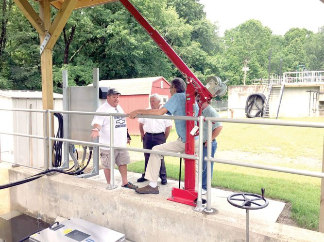 BPA president Kim Adams; county Engineer Bert Dawson; Bruce Lopes of Dallis Dawson and Associates and Councilman Brian Zaverl talk next to the renovated wastewater treatment facility. (Submitted photo)